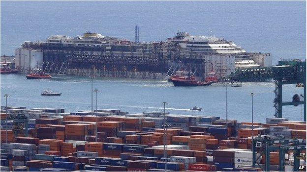 The wreck of the Costa Concordia cruise ship is towed by tugboats into Genoa's harbour