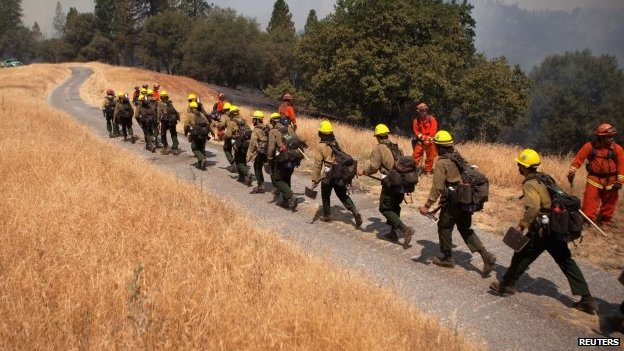 Fire fighters hike in to battle fast-moving wildfire near Plymouth, California (26 July 2014)