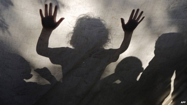 Palestinian children are seen behind a sheet covering a makeshift tent in Gaza City (27 July 2014)