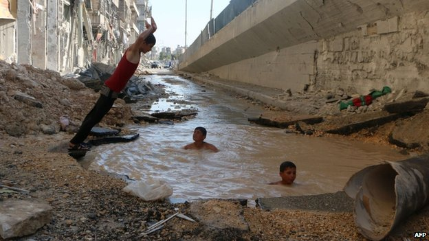 Children playing in a flooded bomb crater in Aleppo (15 July 2014)