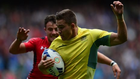 Greg Jeloudev of Australia is chased by Luke Morgan during the Rugby Sevens quarter-final match between Australia and Wales
