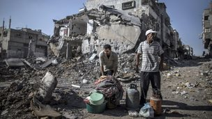 Palestinian men gather things they found in the rubble of destroyed buildings