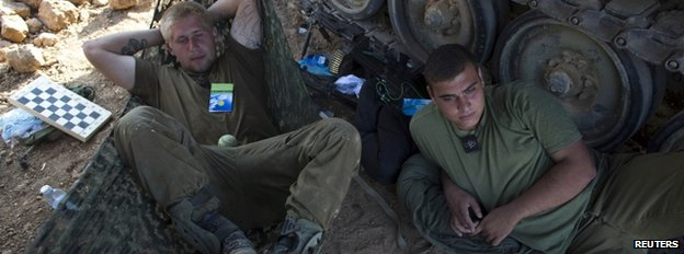 Israeli soldiers rest at a staging area outside the Gaza Strip, 27 July