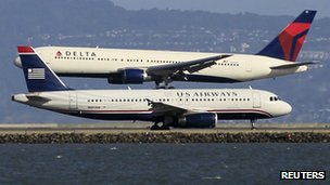 A Delta plane lands as a U.S. Airways plane waits to take off at San Francisco airport,
