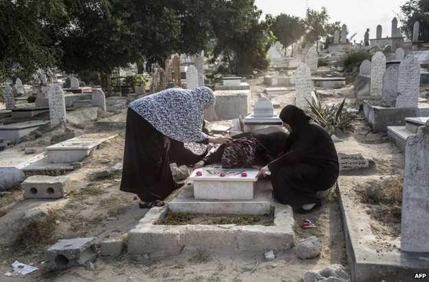Palestinian women visit a grave in Gaza, 28 July