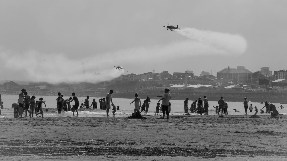 People on a beach enjoy the sunshine while planes fly above them.