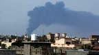Black smoke billows from a fuel storage depot, near the airport in Tripoli, Libya on 28 July 2014, after it was hit by a rocket fire.
