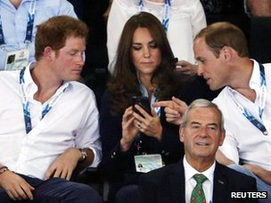 Prince Harry, the Duchess and Duke of Cambridge look at her mobile