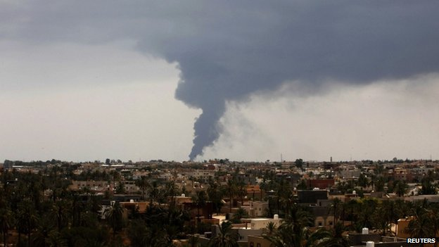 Plumes of smoke rise in the sky after a rocket hit a fuel storage tank near the airport road in Tripoli, during clashes between rival militias on 28 July 2014.