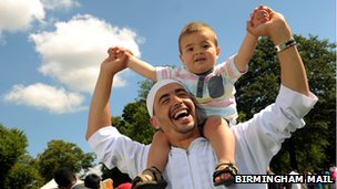 Toddler on his dad's shoulders in Small Heath Park during Eid celebrations