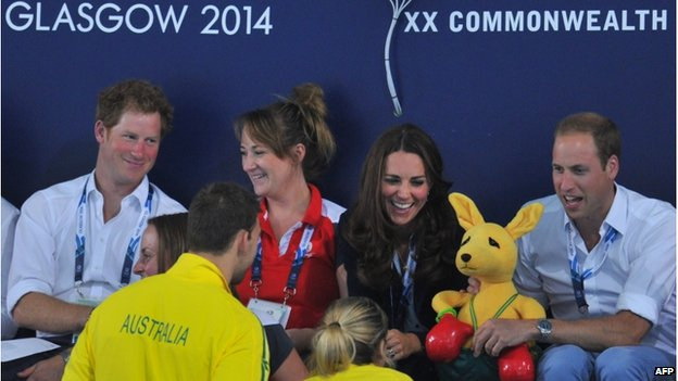 """Prince Harry looks on as Kate and William receive a toy kangaroo from Australia""""s Grant Irvine and Jessica Coroners at Tollcross swimming pool"""