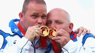 Lawn bowlers Ales Marshall and Paul Foster kiss their gold medals