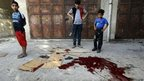 Palestinian children look at a pool of blood from victims of an explosion that killed 10 people at a park at Shati refugee camp in the northern Gaza Strip