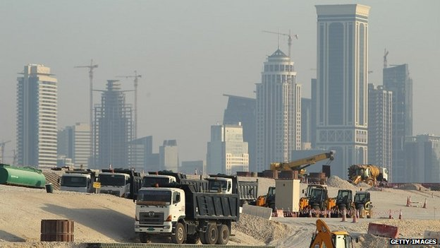 Trucks stand at a construction site across from skyscrapers in the budding new financial district in Doha, Qatar - 26 October 2011