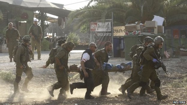 Israeli soldiers carry their comrade on a stretcher after he was wounded in a Palestinian mortar strike, as they evacuate him from the scene outside the central Gaza Strip July 28, 2014
