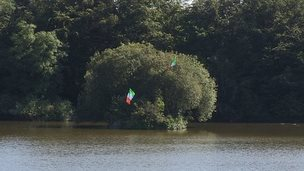Two tricolours were erected on trees last week on an island in Bessbrook Pond