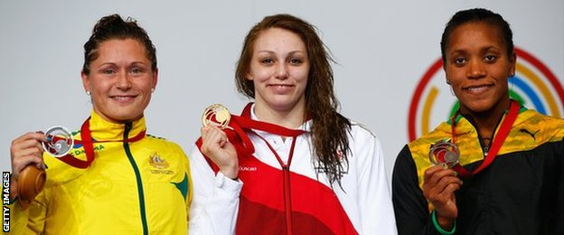 Sophie Taylor of England (centre) with her gold medal alongside silver medallist, Australia's Lorna Tonks and Jamaica's Alia Atkinson with bronze