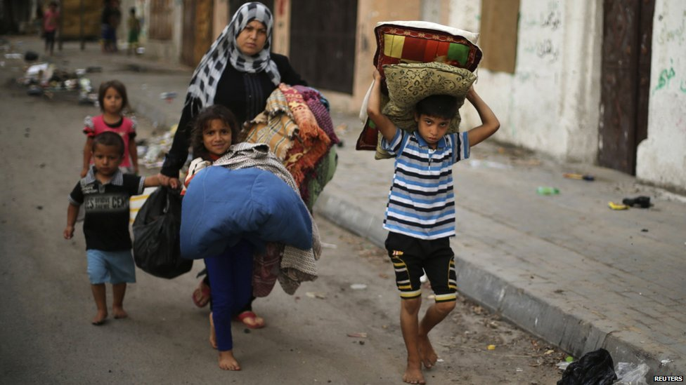 Palestinians carry their belongings as flee their house from what witnesses said were Israeli air strikes, in Gaza City