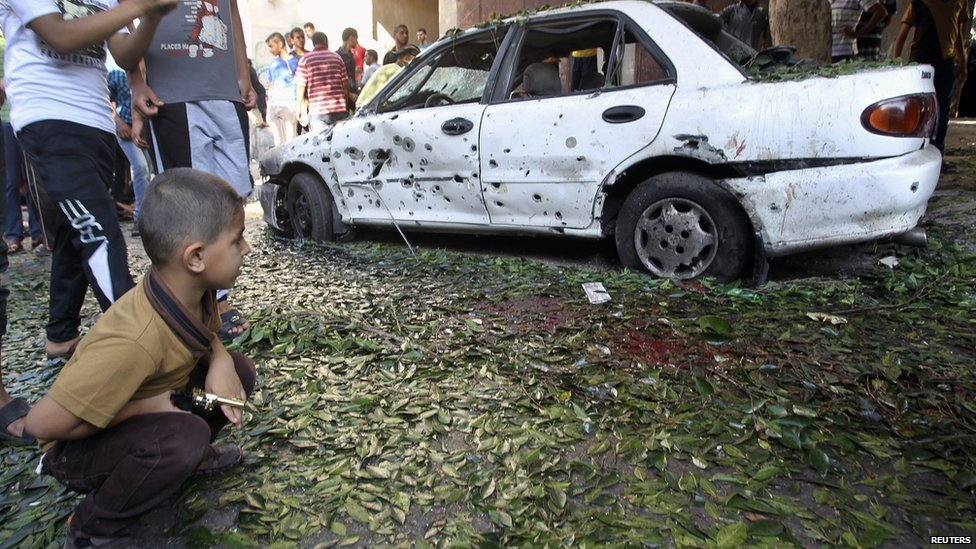 A Palestinian boy looks at a damaged car at the scene of an explosion at a public garden in Gaza City July 28, 2014.