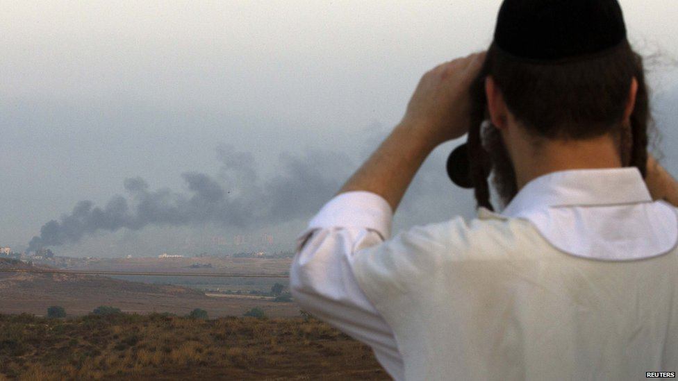 An Israeli man looks through binoculars towards the Gaza Strip near the southern town of Sderot July 29, 2014.