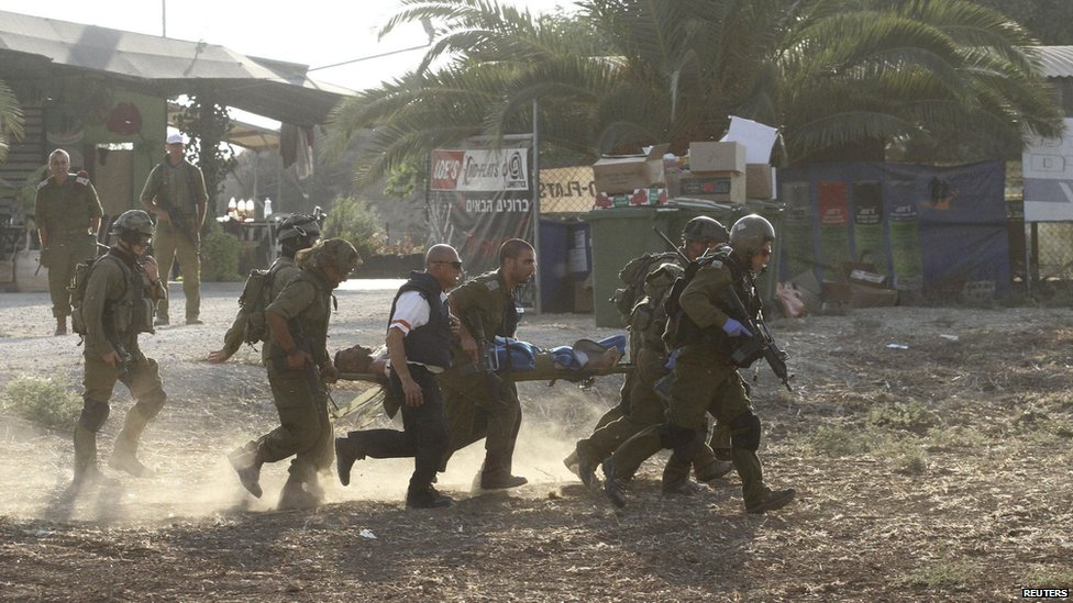 Israeli soldiers carry their comrade on a stretcher after he was wounded in a Palestinian mortar strike, as they evacuate him from the scene outside the central Gaza Strip July 28, 2014.