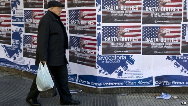 "A man passes posters on a wall against the ""vulture funds"" in Buenos Aires, 18 June 2014"