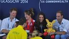 Prince Harry looks on as Kate and William receive a toy kangaroo from Australian swimmers at Tollcross swimming pool