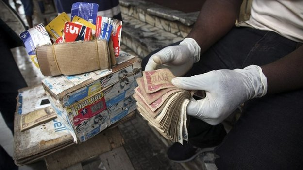 Liberian money exchanger wears protective gloves as a precaution to prevent infection with the deadly Ebola virus while transacting business with customers in downtown Monrovia, Liberia, 28 July 2014