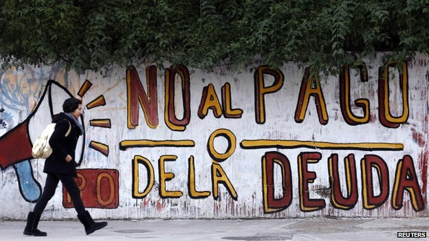 "Woman walks past a graffiti that reads ""No to the debt payment"" in Buenos Aires, 28 July 2014"