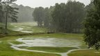 A green golf course completely drenched in water from the torrential downpours. Green trees scattered around wilt under the water and large puddles form a lake like effect running through the centre of the golfing green.