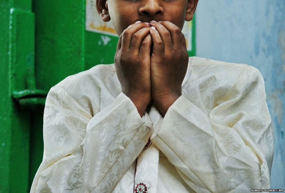 An Indian Muslim child prays as he stands near the entrance to a mosque, as he and other devotees congregated to celebrate the Eid al-Fitr festival, in southern Delhi 29 July 2014
