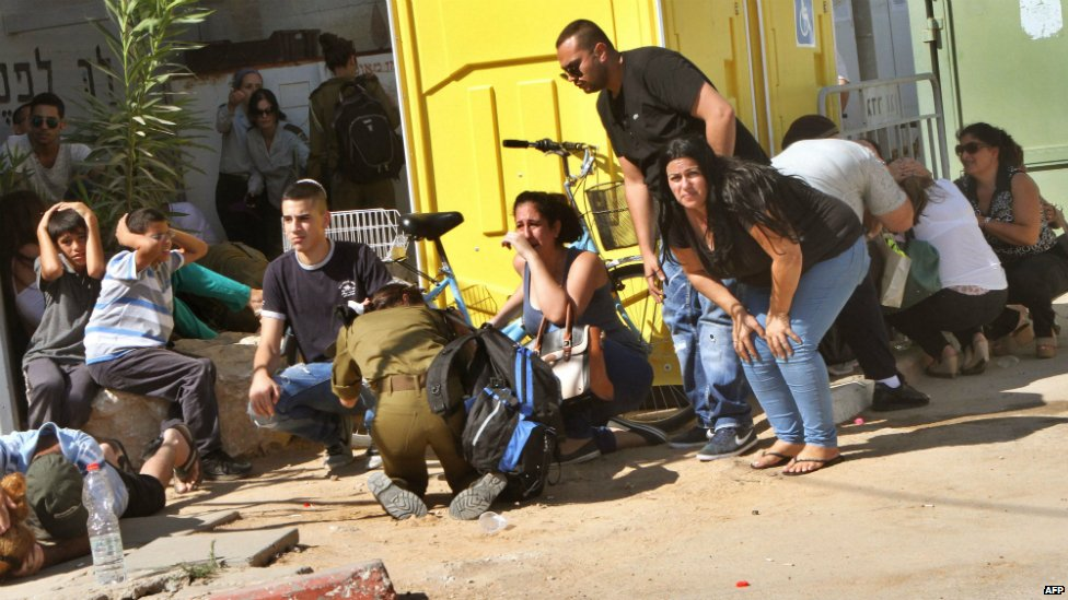 Israeli residents take cover from a rocket attack during the funeral of Israeli soldier Corporal Meidan Maymon Biton, 20, at a cemetery in Netivot - 29 July 2014