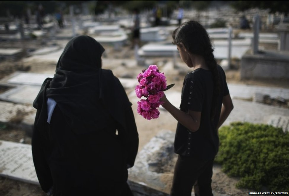 A Palestinian woman and a girl carry flowers to a family grave on Eid al-Fitr at a cemetery in Gaza City