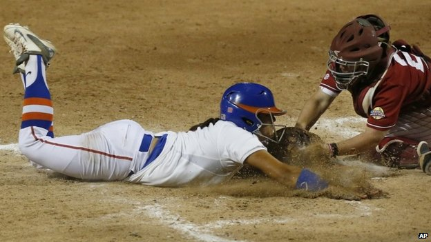 Alabama catcher Molly Fichtner (22) tags out Florida's Stephanie Tofft, left, at home plate in the sixth inning of an NCAA Women's College World Series softball tournament game in Oklahoma City, 3 June 2014