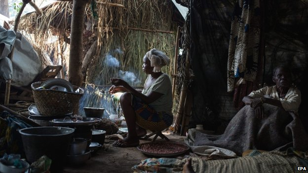 A displaced Christian woman cooks dinner at the largest displacement site located outside the French military base in Bambari, Central African Republic - 27 July 2014