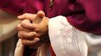 Hands of clergy in prayer
