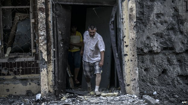 Man leaving bombed-out house in Donetsk, 29 Jul 14