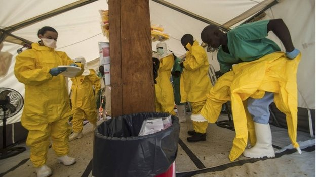 Medical staff working with Medecins sans Frontieres (MSF) put on their protective gear before entering an isolation area at the MSF Ebola treatment centre in Kailahun on 20 July 2014