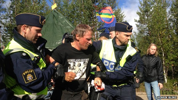 Anti-mine protester being held by two police