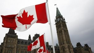Canadian flags line the road around Parliament Hill during the National Day of Honour ceremony in Ottawa 9 May 2014