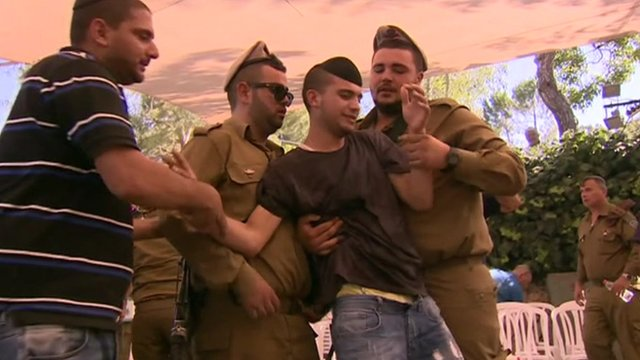 Israeli soldiers support a man