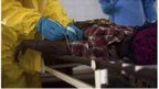 Medical staff take a blood sample from a suspected Ebola patient at the government hospital in Kenema, Sierra Leone