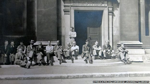 Workers rest on the steps of the old library