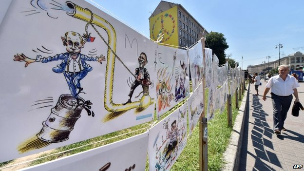 A man walks past caricatures of Russian President Vladimir Putin at an open-air exhibition by Ukrainian cartoonist, architect and journalist Oleh Smal, in the center of Kiev on 29 July 2014.