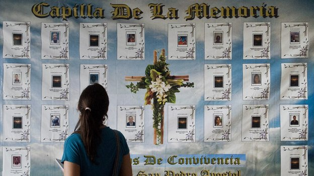 A woman looks at a banner with pictures of victims of violence in the port of Buenaventura on 26 March, 2014.