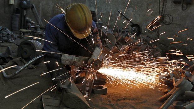 A worker grinds a metal shaft metal used in water pumps at a manufacturing unit
