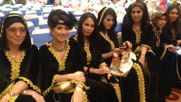 Beautifully dressed ladies sitting in a line at a social event