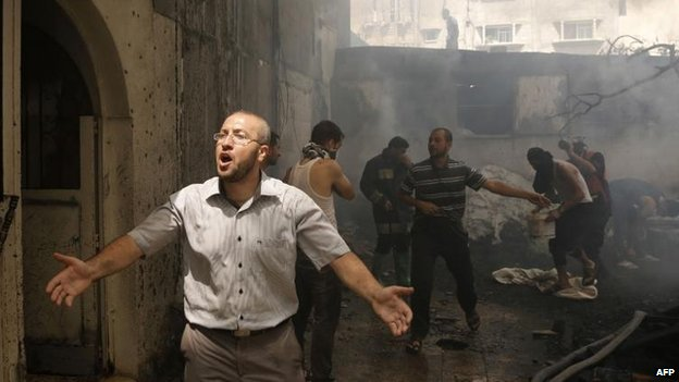 Palestinians try to put out a fire in Gaza City after an Israeli air strike, 30 July