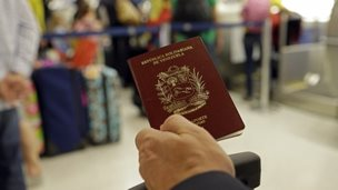 A man holds a Venezuelan passport in this photo taken on 25 June, 2014