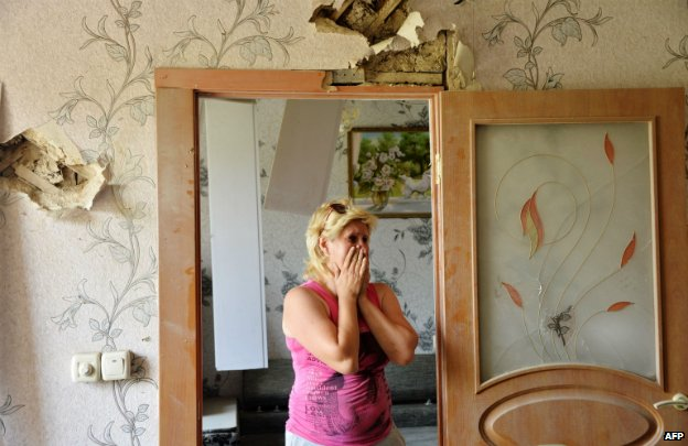 A woman cries in her damaged house in the eastern Donetsk region - 30 July 2014